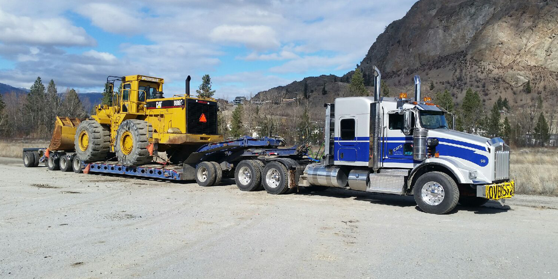 lowbed hauling truck with yellow tractor