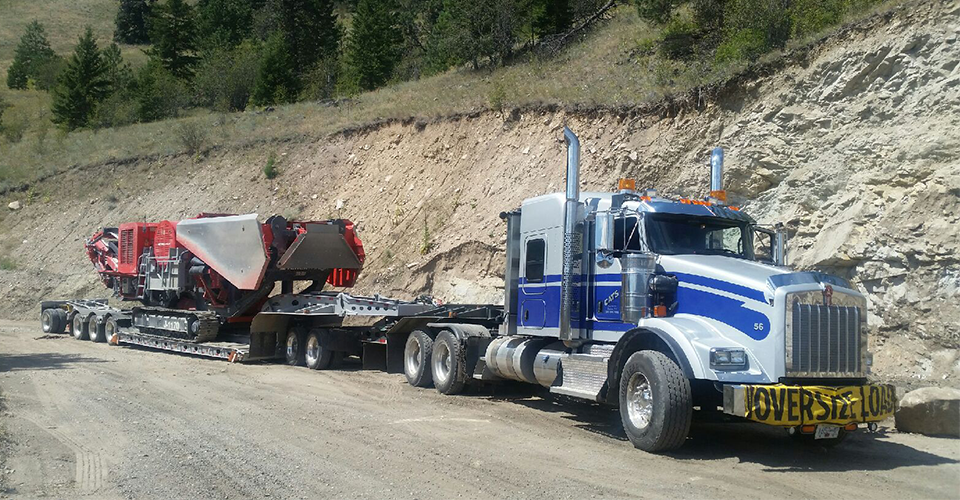 silver trailer truck hauling equipments downhill